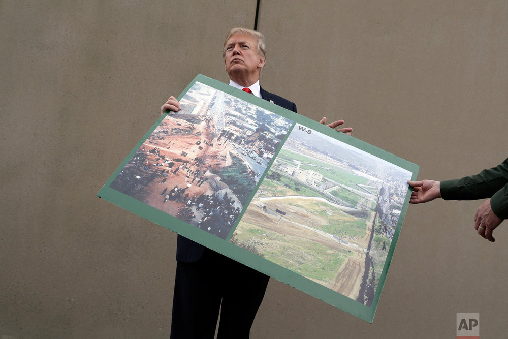 President Donald Trump holds a photo of the border area as he reviews border wall prototypes, Tuesday, March 13, 2018, in San Diego. Rodney Scott, the Border Patrol's San Diego sector chief, helps to hold the print. (AP Photo/Evan Vucci)