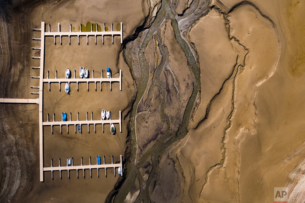 Stranded boats lie on the surface of the dried-out shores of the Lake of Gruyere in La Roche near Bulle, Switzerland, Wednesday, March 14, 2018. The level of the artificial impounding reservoir is progressively being reduced by 15 to 20 meters, in anticipation of meltwater from heavy snowfall accumulated on the surrounding mountains. (Valentin Flauraud/Keystone via AP)