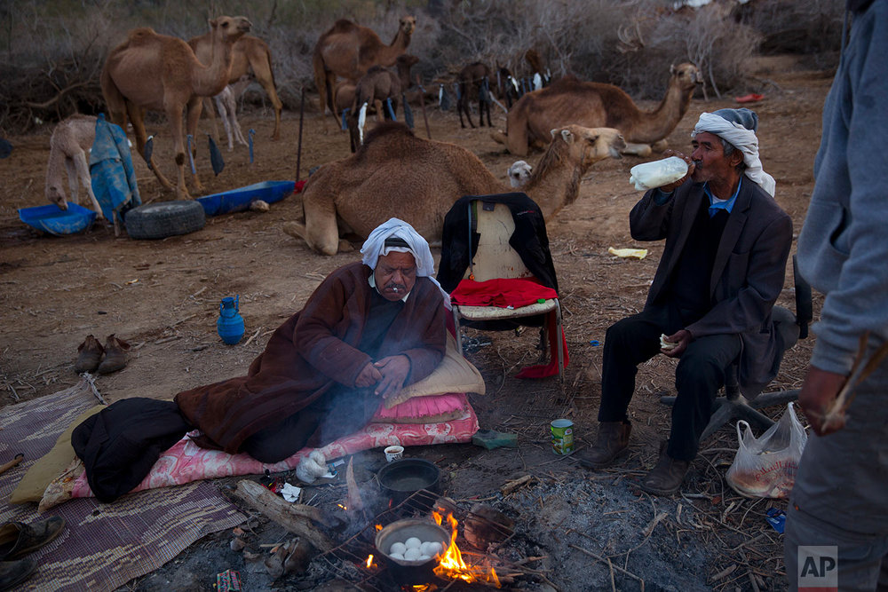 In this Saturday, Feb. 10, 2018 photo, Beduin camels owner Ali El Guran, left, and his camels herder Salem Rashaideh, have their breakfast at the night camp at the territory of Israeli Kibbutz Kalya, near the Dead Sea in the West Bank. (AP Photo/Oded Balilty)