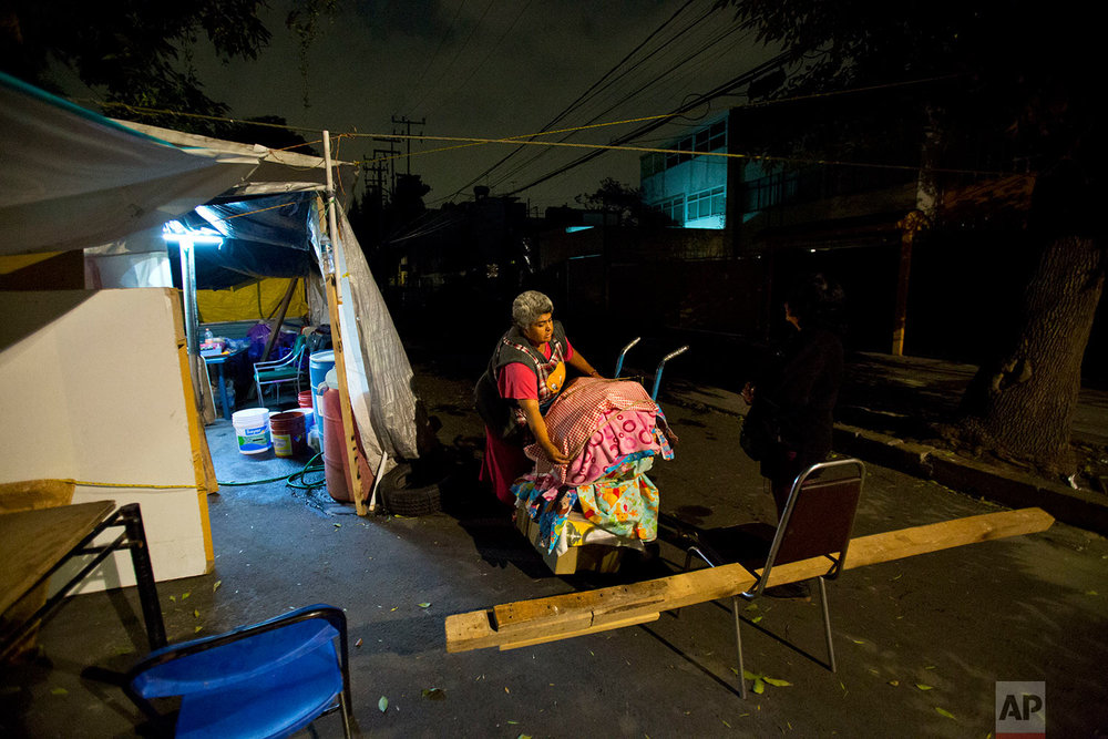 Vendor Maria Patricia Rodriguez Gonzalez packs up her wares to bring them in for the night, at the tent camp where she has been living with her family for the last six months, outside her earthquake-damaged residence at Independencia 18 in Mexico City, March 14, 2018. (AP Photo/Rebecca Blackwell)