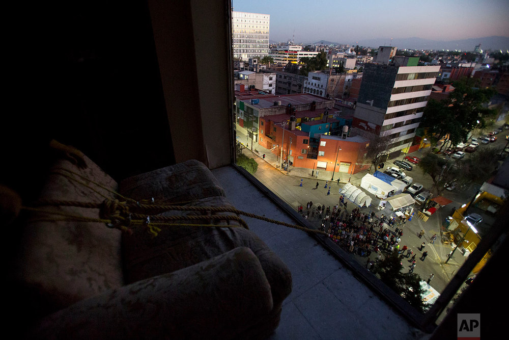 "Movers prepare to lower a couch out through the missing windows of an apartment inside the condemned ""Great Bear"" building, the first within the complex to be demolished after the 2017 earthquake, in the Doctores neighborhood of Mexico City, Jan. 11, 2018. (AP Photo/Rebecca Blackwell)"
