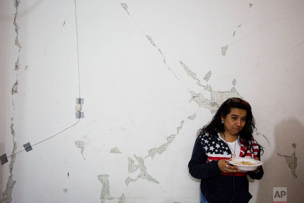 "In this Jan. 12, 2018 photo, a woman eats hot noodle soup provided by volunteers from earthquake-relief organization ""Ayudame Hoy,"" inside an earthquake-damaged building in southern Mexico City. (AP Photo/Rebecca Blackwell)"