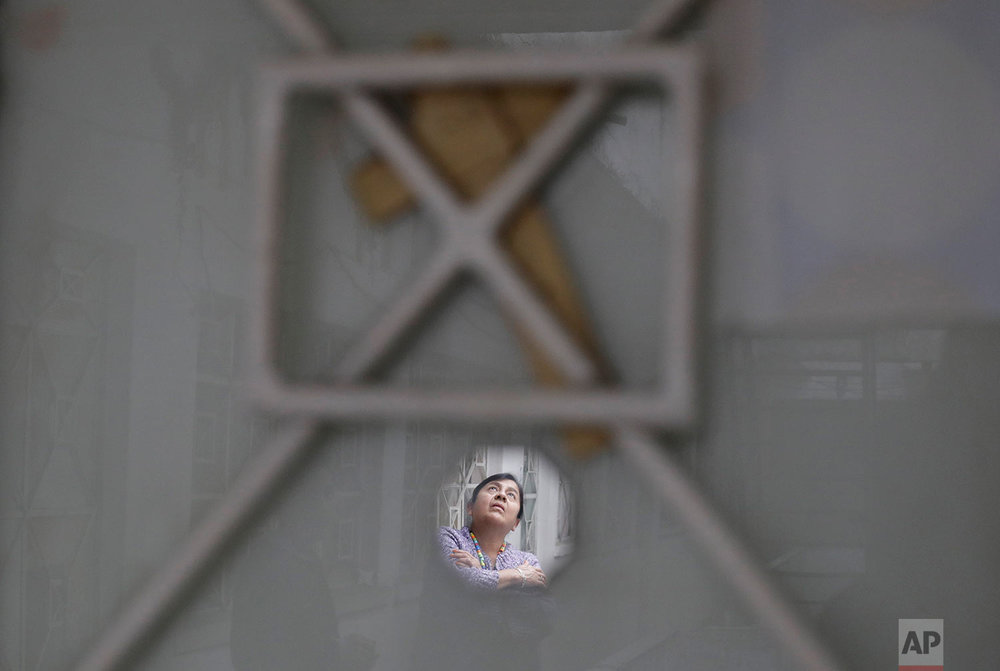 In this Jan. 5, 2018 photo, Luz Maria Alvarez Lopez, 50, is reflected in the small mirror which adorns her apartment's front door along with a simple reed cross, in the earthquake damaged building at Independencia 18 in Mexico City where she has lived for 29 years and where her family uses four of its 37 apartments. (AP Photo/Rebecca Blackwell)
