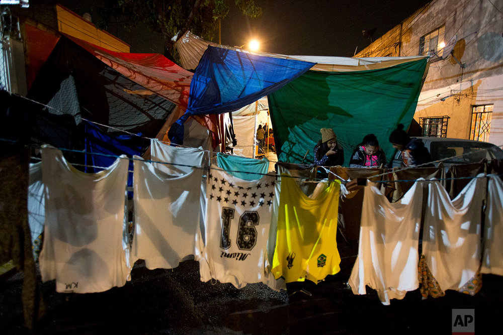 In this Jan. 12, 2018 photo, clothing hangs to dry in a tent camp where teenagers pass the time looking at a cell phone outside the earthquake-damaged Independencia 18 residence at night in Mexico City. (AP Photo/Rebecca Blackwell)