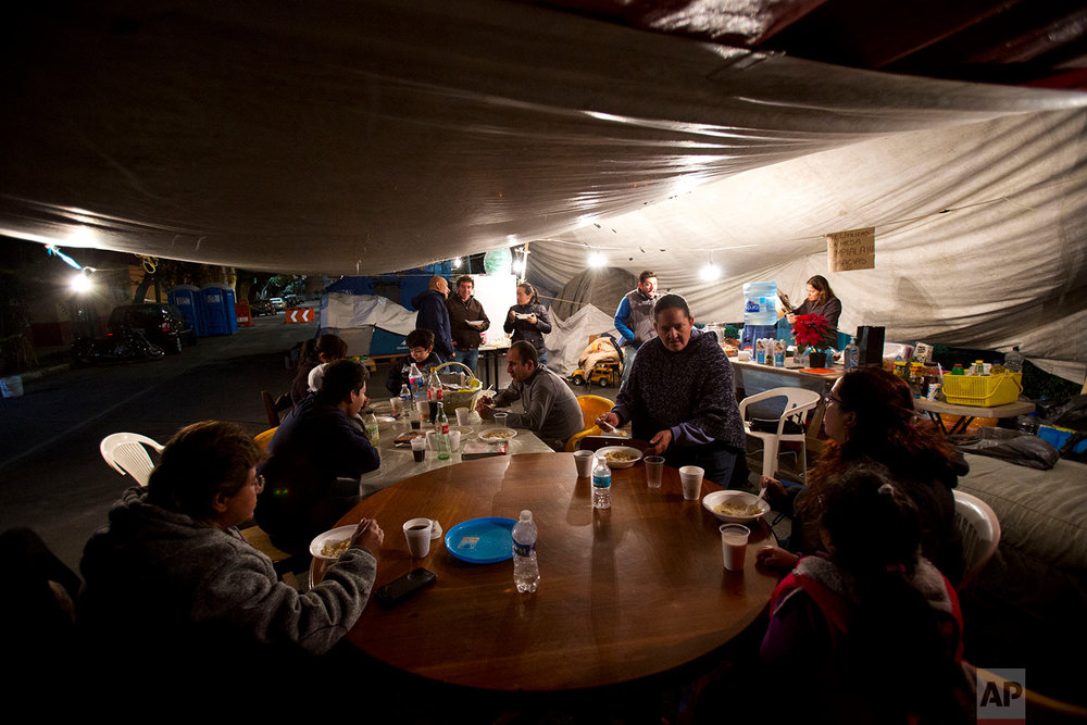 "In this Jan. 12, 2018 photo, residents of an earthquake-damaged apartment building at 5 de Febrero and Guipuzcoa gather for a hot dinner brought by volunteers from the earthquake relief group ""Ayudame Hoy,"" in the tent camp where they have been living outside their building in Mexico City. (AP Photo/Rebecca Blackwell)"