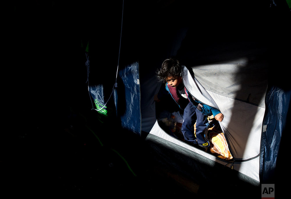 In this March 13, 2018 photo, four-year-old Yandel Rivera climbs out of the tent where he is living with his family outside earthquake-damaged Independencia 18 in Mexico City.  (AP Photo/Rebecca Blackwell)