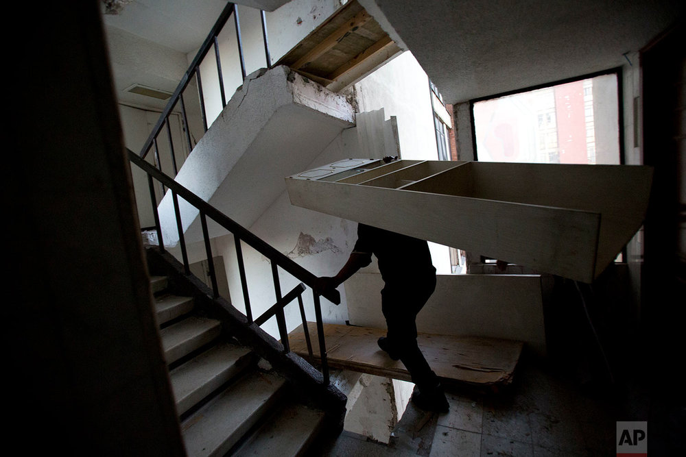 In this Jan. 11, 2018 photo, a man carries a bookshelf down a staircase with gaps that have been covered with boards, as a handful of residents accompanied by movers brave a 15-story condemned building to recover personal possessions and furniture, in the Doctores neighborhood of Mexico City. (AP Photo/Rebecca Blackwell)