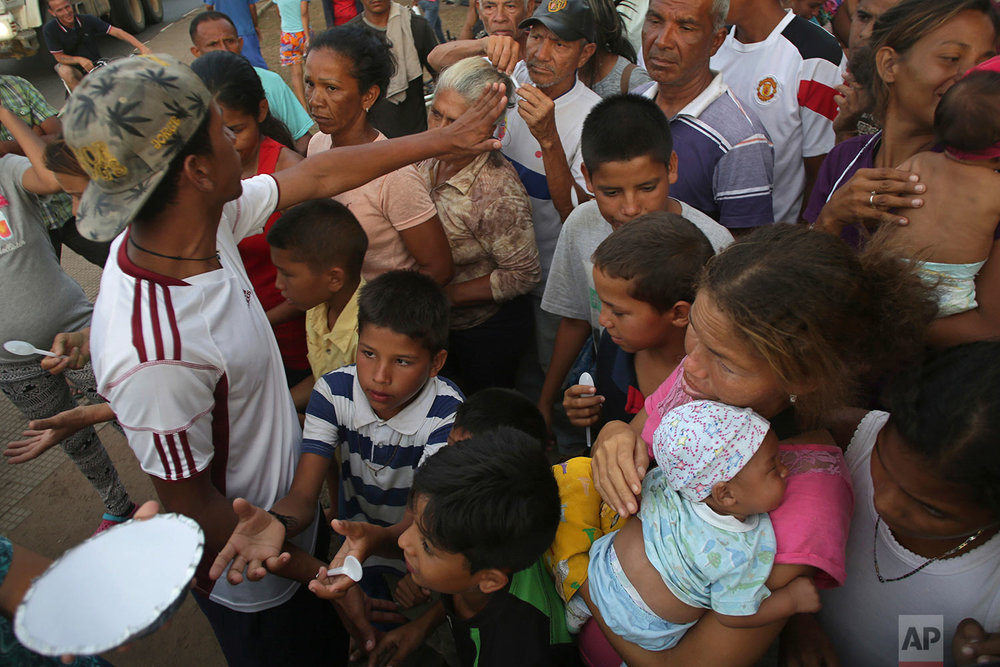 Venezuelan migrants wait for a free meal in Simon Bolivar Square, a park at an intersection where many have set up tents in Boa Vista, Roraima state, Brazil, March 8, 2018. (AP Photo/Eraldo Peres)