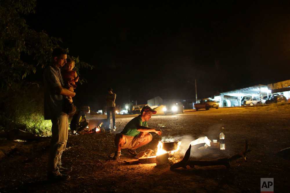 Venezuelans cook food on the side of Highway BR 147 after crossing the Venezuela-Brazil border in Pacaraima, Roraima state, Brazil, March 9, 2018. (AP Photo/Eraldo Peres)