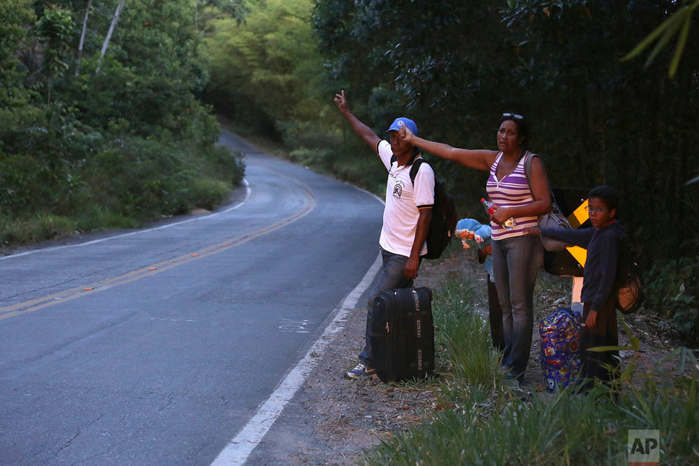 Venezuelan couple Jose Guillen and July Bascelta hitch-hike with their 9-year-old twins Angel David and Ashley Angelina along Highway BR 147 after crossing the border into Brazil near Pacaraima, Roraima state, Brazil, March 9, 2018. (AP Photo/Eraldo Peres)