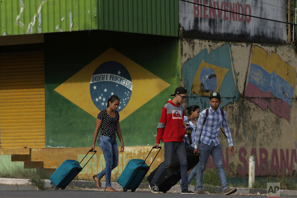 In this March 9, 2018 photo, young Venezuelans pull their luggage after crossing the border to Pacaraima, Roraima state, Brazil. (AP Photo/Eraldo Peres)