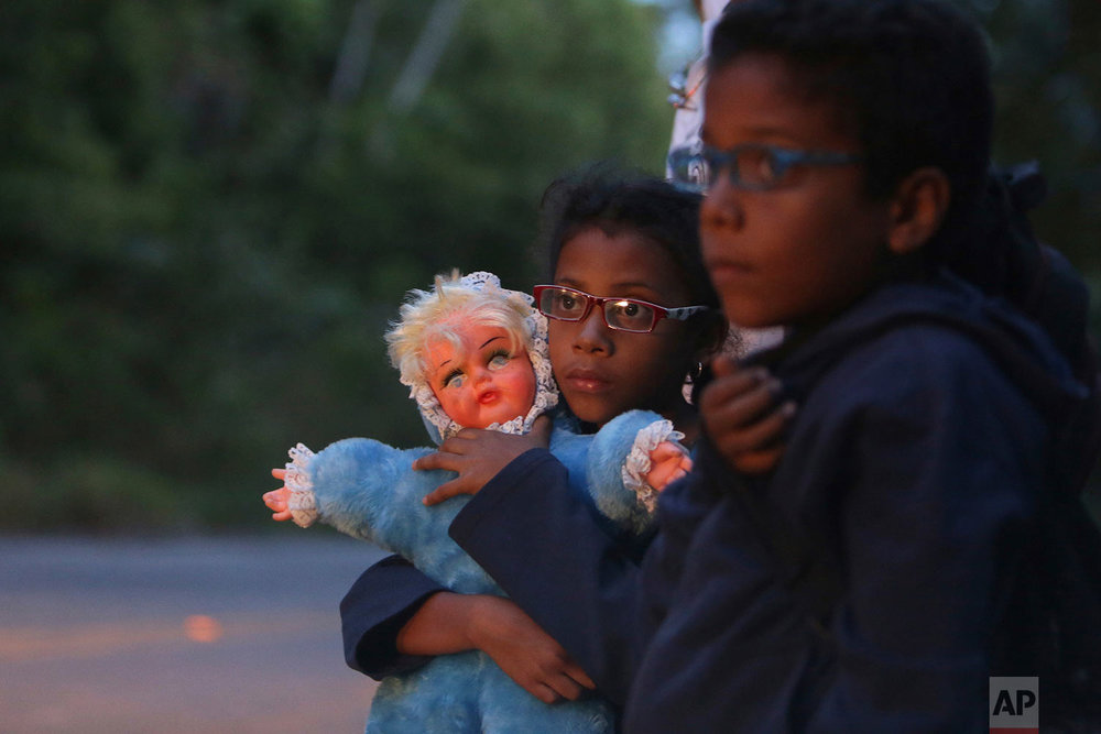 In this March 9, 2018 photo, 9-year-old Ashley Angelina holds her doll as she hitch-hikes with her twin brother Angel David and their parents along Highway BR 147 after crossing the Venezuelan border as they migrate to Brazil near Pacaraima, Roraima state, Brazil. (AP Photo/Eraldo Peres)