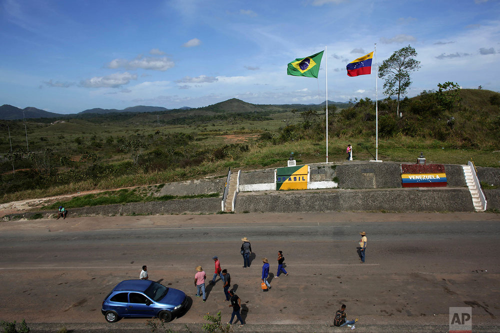 In this March 10, 2018 photo, people stand at the border between Venezuela, right, and Brazil, near the Brazilian city of Pacaraima, Roraima state. (AP Photo/Eraldo Peres)