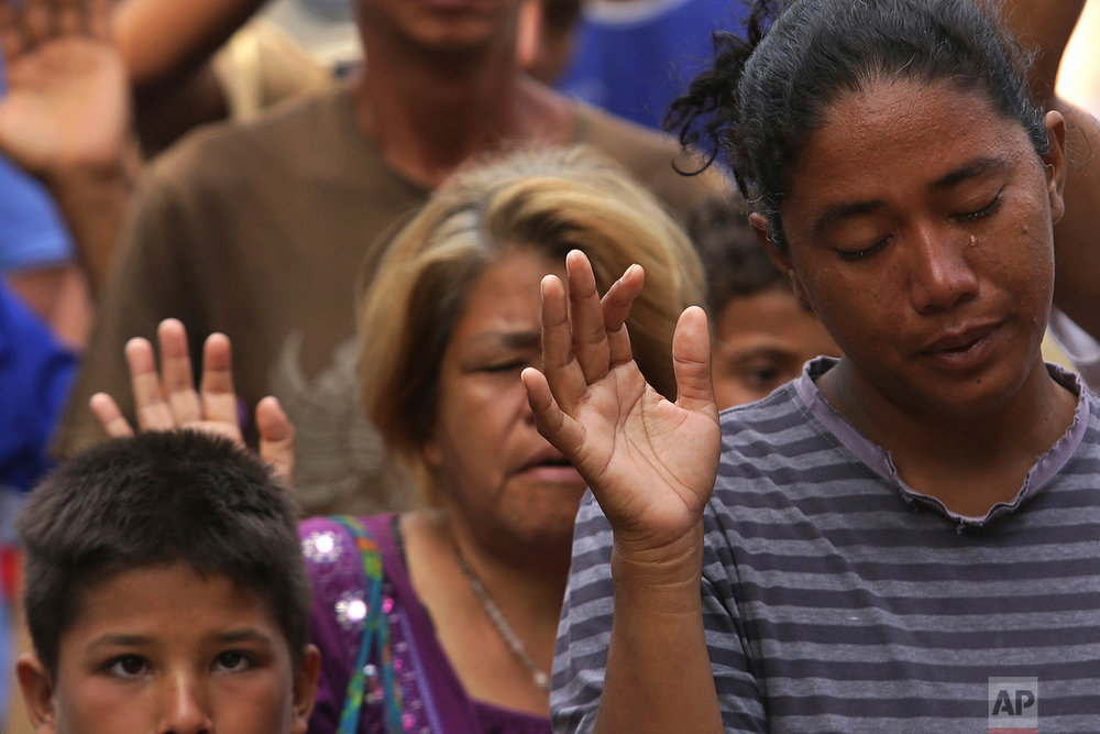 In this March 11, 2018 photo, a tear runs down the cheek of Venezuelan woman praying during religious service in Simon Bolivar Square where many are living in tents in Boa Vista, Roraima state, Brazil. (AP Photo/Eraldo Peres)