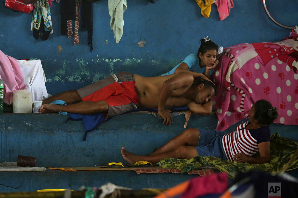 In this March 8, 2018 photo, a Venezuelan family rests in a shelter set up inside the Tancredo Neves Gymnasium in Boa Vista, Roraima state, Brazil. (AP Photo/Eraldo Peres)