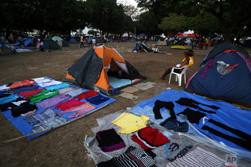 In this March 11, 2018 photo, clothing lays out to dry at a camp set up by Venezuelan migrants living in Simon Bolivar Square in Boa Vista, Roraima state, Brazil. (AP Photo/Eraldo Peres)