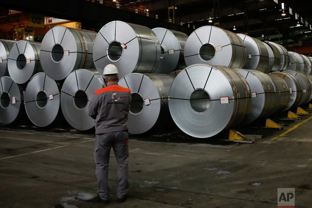 An employee stands in front of coils at the steel producer,  Salzgitter AG, in Salzgitter, Thursday, March 22, 2018. (AP Photo/Markus Schreiber)