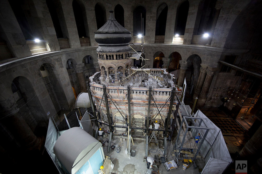 In this Monday, Sept. 19, 2016 photo, a Greek conservation team renovate the Tomb of Jesus in the Church of the Holy Sepulchre in Jerusalem's Old City.  (AP Photo/Oded Balilty)