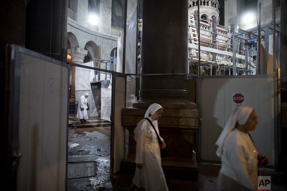 In this Thursday, Oct. 27, 2016 photo, Christian nuns walk next to the Edicule during the renovation of the Tomb of Jesus in the Church of the Holy Sepulchre in Jerusalem's Old City.  (AP Photo/Oded Balilty)