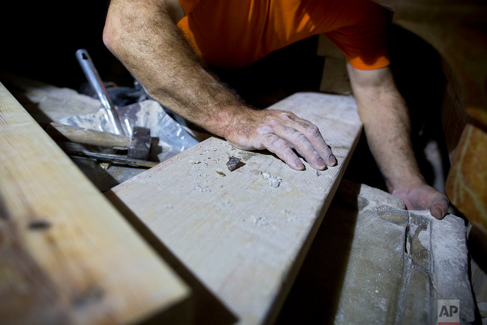 In this Friday, Oct. 28, 2016 photo, a restorer removes debris beneath a broken marble slab to expose the original rock surface of what is considered the burial place of Jesus in the Church of the Holy Sepulchre during its renovation in Jerusalem's Old City.  (AP Photo/Oded Balilty)