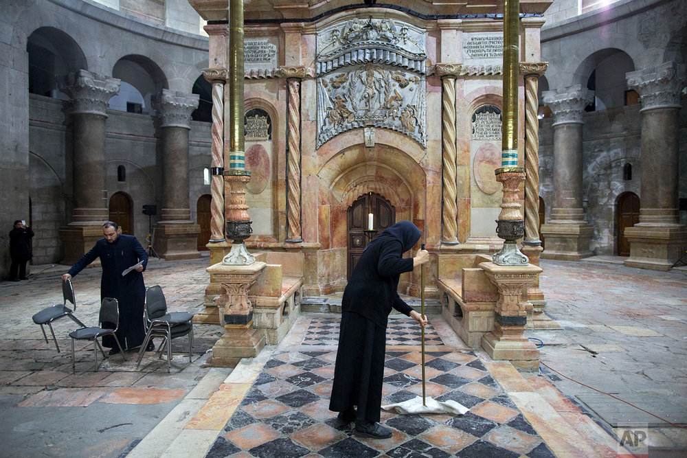 A nun cleans the area around the  renovated Edicule ahed of a ceremony marking the completion of the renovation in the Church of the Holy Sepulchre, in Jerusalem's Old City, Wednesday, March 22, 2017. (AP Photo/Oded Balilty)