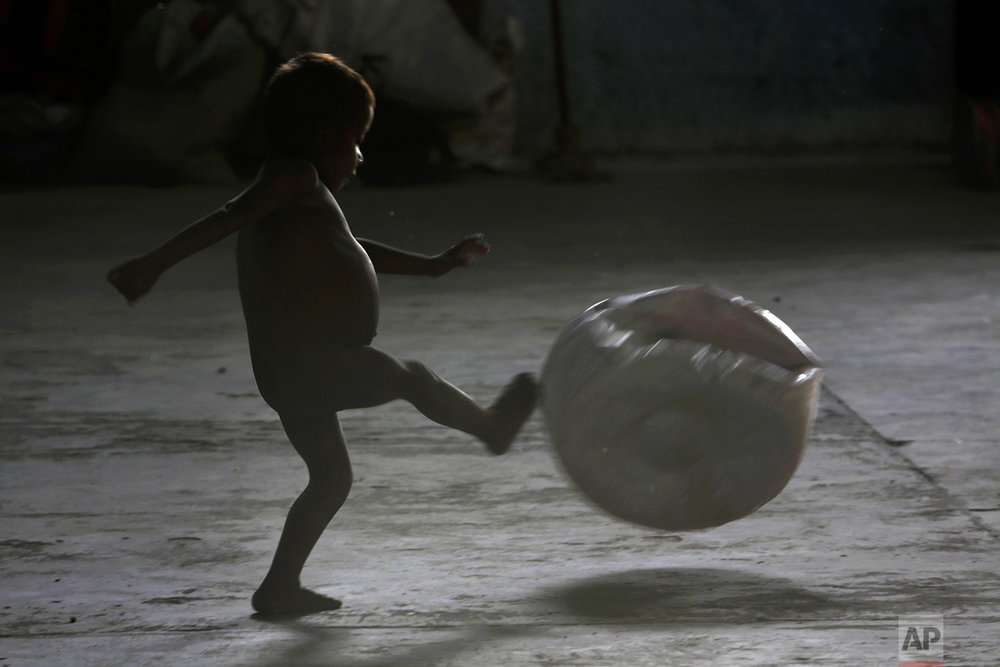 In this March 10, 2018 photo, 2-year-old Warao Ricardo Zapata kicks an inflatable ball inside a shelter, in Pacaraima, Brazil. (AP Photo/Eraldo Peres)
