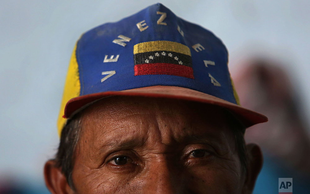 In this March 10, 2018 photo, Warao Cesar Mariano, 58, from Venezuela, wears a cap featuring the national flag of his native country, at a shelter, in Pacaraima, Brazil. (AP Photo/Eraldo Peres)