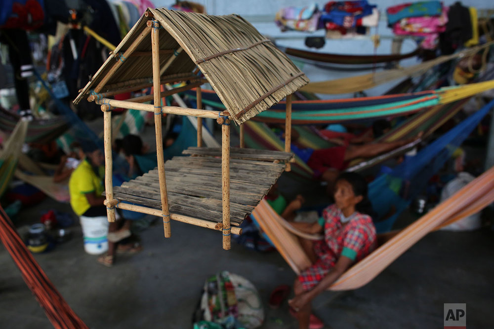 This March 10, 2018 photo shows an adornment depicting a traditional Warao thatched roof hut made from palm fibers hanging inside a shelter, in Pacaraima, Brazil. (AP Photo/Eraldo Peres)