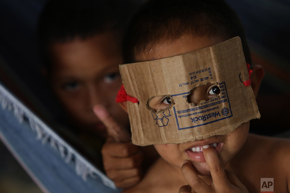 In this March 10, 2018 photo, a Warao boy from Venezuela dons a mask fashioned from cardboard in a shelter, in Pacaraima, Brazil. (AP Photo/Eraldo Peres)