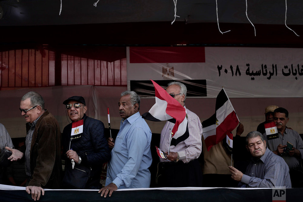 Egyptian men wave national flags as they wait in line to vote during the first day of the presidential election in front of a polling site in Cairo, Egypt, Monday, March 26, 2018.  Egyptians head to the polls on Monday but the presidential election this time is not about who wins — that was settled long ago — but about how many people bother to cast ballots. (AP Photo/Nariman El-Mofty)
