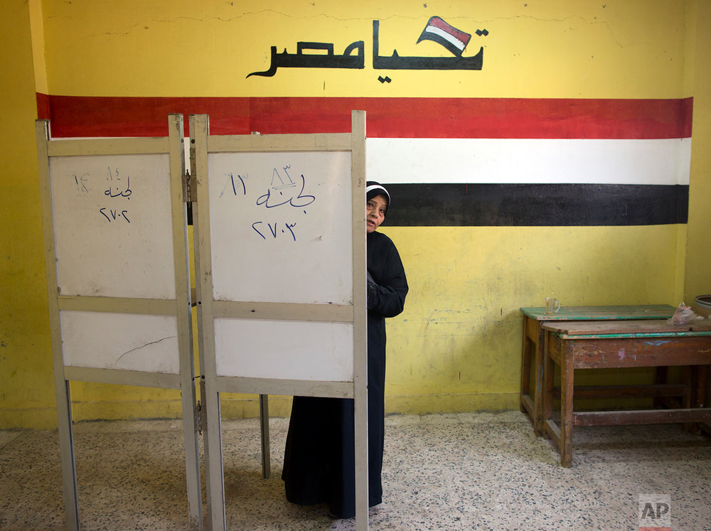 A woman prepares to vote during the second day of the presidential election at a polling station in Cairo, Egypt, Tuesday, March 27, 2018. Egyptians are voting for a second day in a lackluster election that President Abdel-Fattah el-Sissi is virtually certain to win after all serious rivals were either arrested or intimidated into dropping out ahead of the balloting. (AP Photo/Amr Nabil)