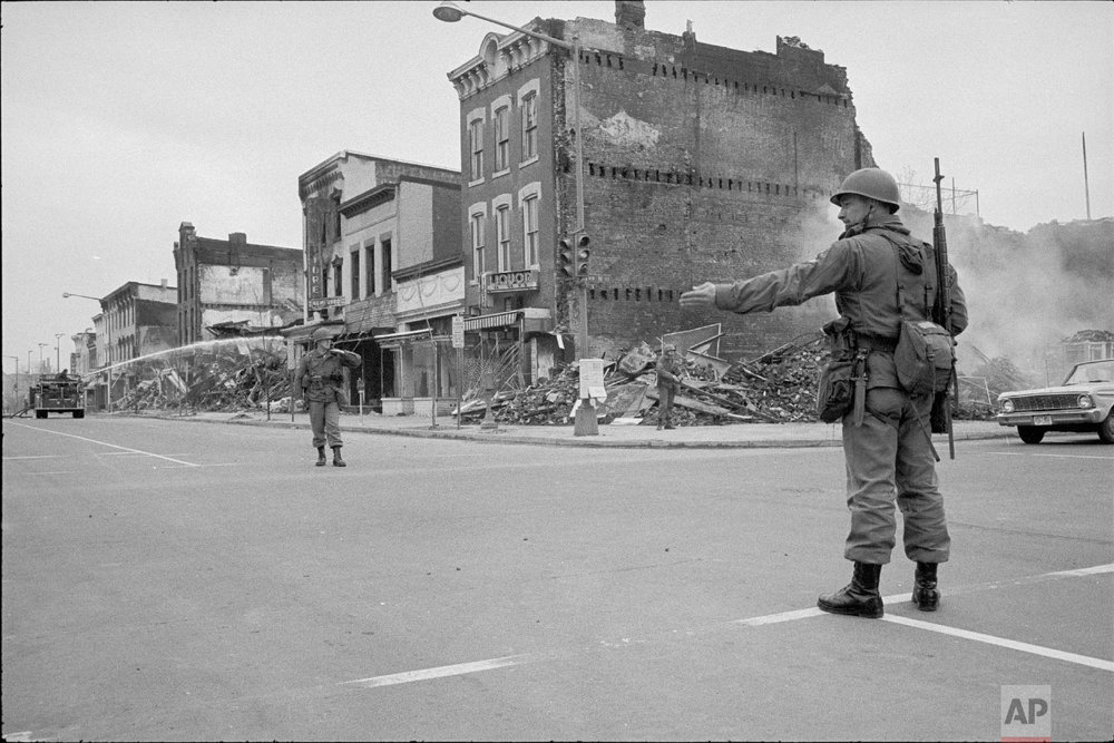 Photograph showing a soldier standing guard at 7th and N Street, N.W., Washington, D.C., Monday, April 8, 1968, with the ruins of buildings that were destroyed during the riots that followed the assassination of Martin Luther King, Jr. (Photo/ Warren K. Leffler/Library of Congress)