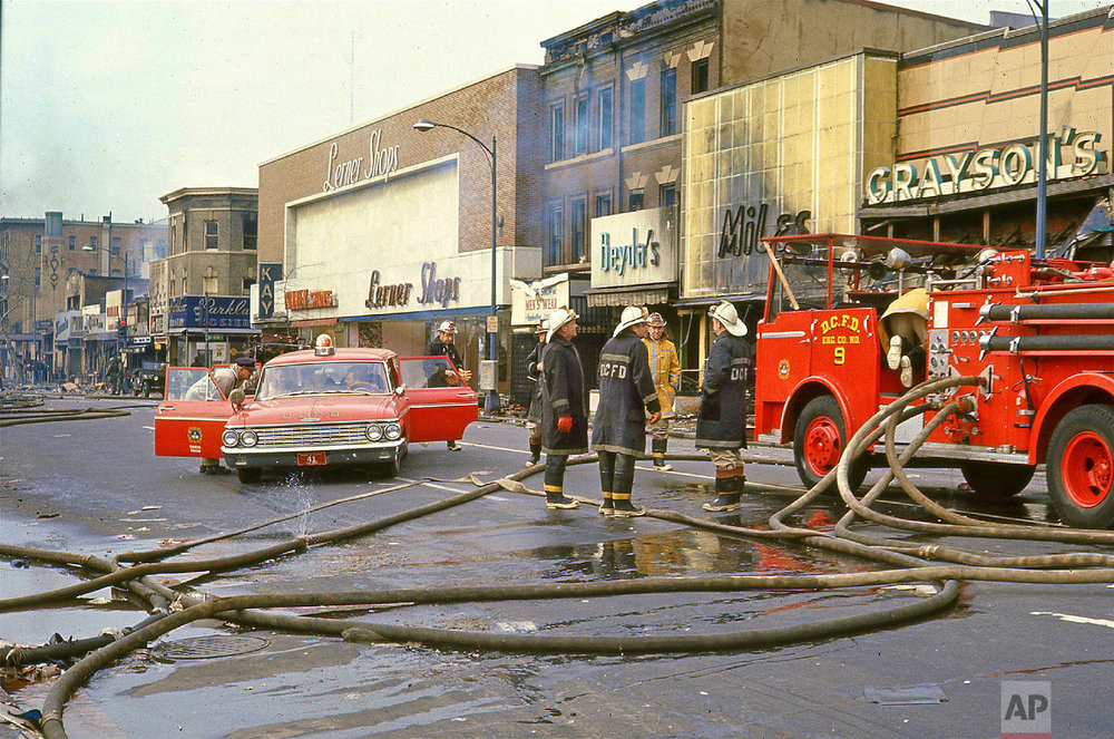 14th Street near Irving Street, 1968. Firemen gathered at a fire engine on 14th Street near Irving Street following rioting after the assassination of Dr. Martin Luther King, Jr., Saturday, April 6, 1968. Firehouses cover the ground. Burned storefronts stand in the background. (Photo/Darell C. Crain/ DC Public Library Specials Collection)