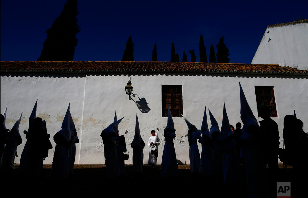 "Hooded penitents from the ""La Paz"" brotherhood take part during Holy Week procession in Cordoba, southern Spain, Wednesday, March 28, 2018. Hundreds of processions take place throughout Spain during the Easter Holy Week. (AP Photo/Manu Fernandez)"