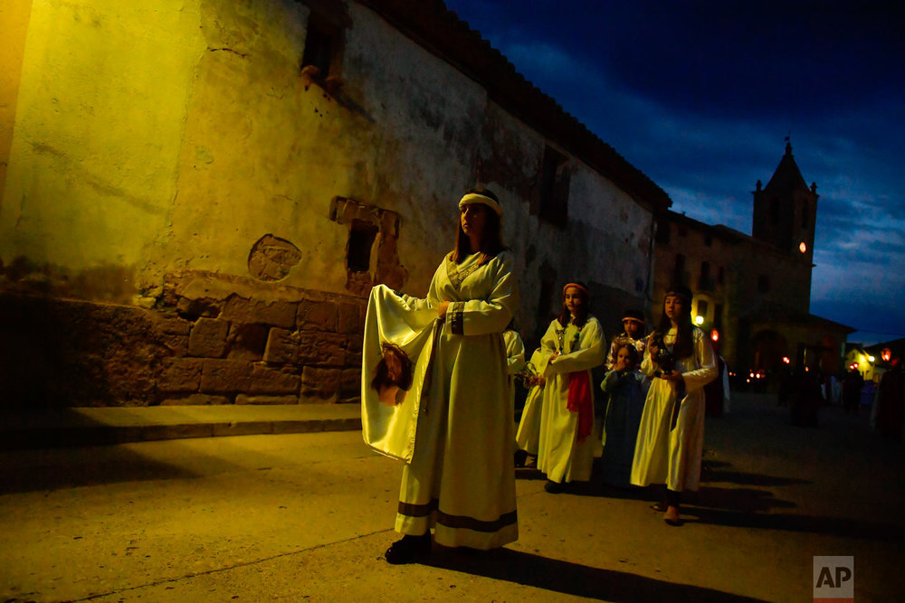 Devotes take part in the procession of ''El Ensogado'' during the Holy Week in Sietamo, northern Spain, Thursday, March 29, 2018. For days leading up to Easter Sunday each year, hundreds of colorful processions featuring penitents and magnificently decorated religious floats parade through the streets of villages and cities across the country, celebrating the Passion of Christ from the crucifixion to resurrection, celebrations which have become a major tourist attraction and televised nationwide. (AP Photo/Alvaro Barrientos)