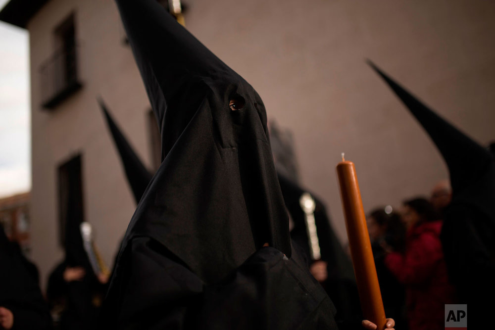 "Hooded penitents from ""Los Estudiantes"" brotherhood take part in a traditional annual Holy Week procession in Madrid, Sunday, March 25, 2018. Hundreds of processions take place throughout Spain during the Easter Holy Week. (AP Photo/Francisco Seco)"