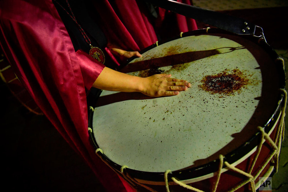 "A penitent puts the hand on a drum while taking part in a procession of the ""Santa Veracruz"" brotherhood, during the Holy Week in Calahorra, northern Spain, Wednesday, March 28, 2018. Hundreds of processions take place throughout Spain during the Easter Holy Week. (AP Photo/Alvaro Barrientos)"