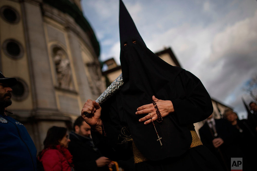 "A hooded penitent from ""Los Estudiantes"" brotherhood holds a rosary with a small cross as taking part in a traditional annual Holy Week procession in Madrid, Sunday, March 25, 2018. Hundreds of processions take place throughout Spain during the Easter Holy Week. (AP Photo/Francisco Seco)"