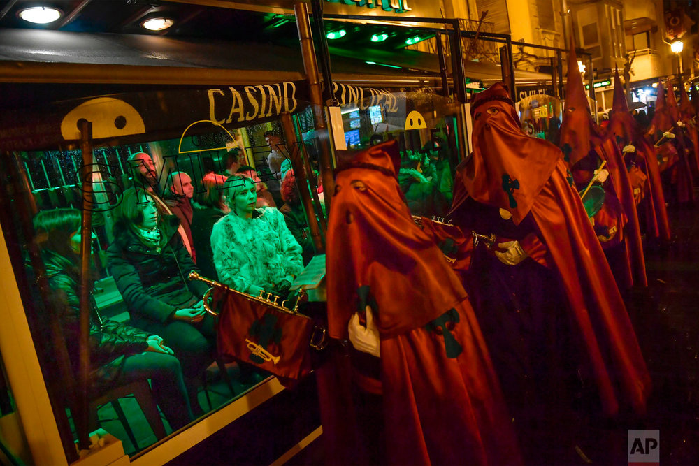 "People watch penitents from a bar during a procession of the ""Santa Veracruz"" brotherhood, during the Holy Week in Calahorra, northern Spain, Wednesday, March 28, 2018. Hundreds of processions take place throughout Spain during the Easter Holy Week. (AP Photo/Alvaro Barrientos)"