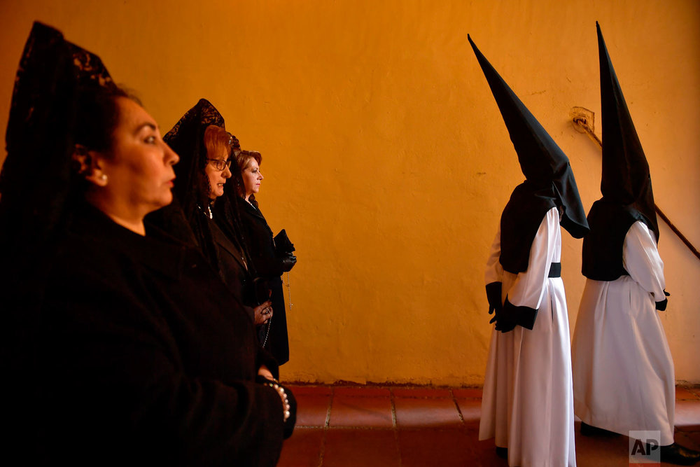 "Penitents and devotes known as ''Las Manolas'' take part in the procession of the ""Exaltacion de La Santa Cruz"" brotherhood, during Holy Week in Zaragoza, northern Spain, Thursday, March 29, 2018. Hundreds of processions take place throughout Spain during the Easter Holy Week. (AP Photo/Alvaro Barrientos)"