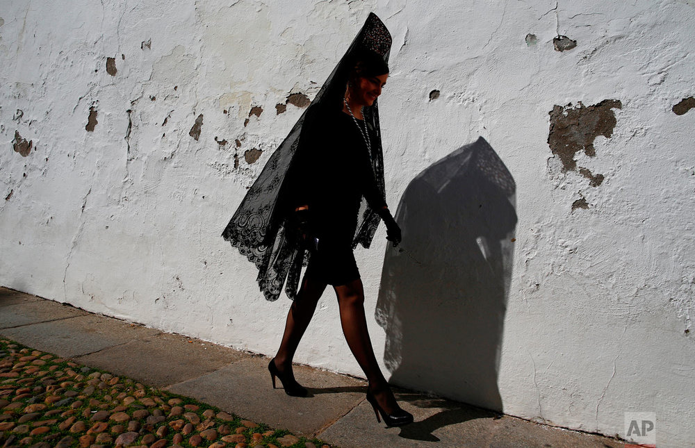 "A woman wearing the traditional mantilla from the ""La Paz"" brotherhood takes part during Holy Week procession in Cordoba, southern Spain, Wednesday, March 28, 2018. Hundreds of processions take place throughout Spain during the Easter Holy Week. (AP Photo/Manu Fernandez)"