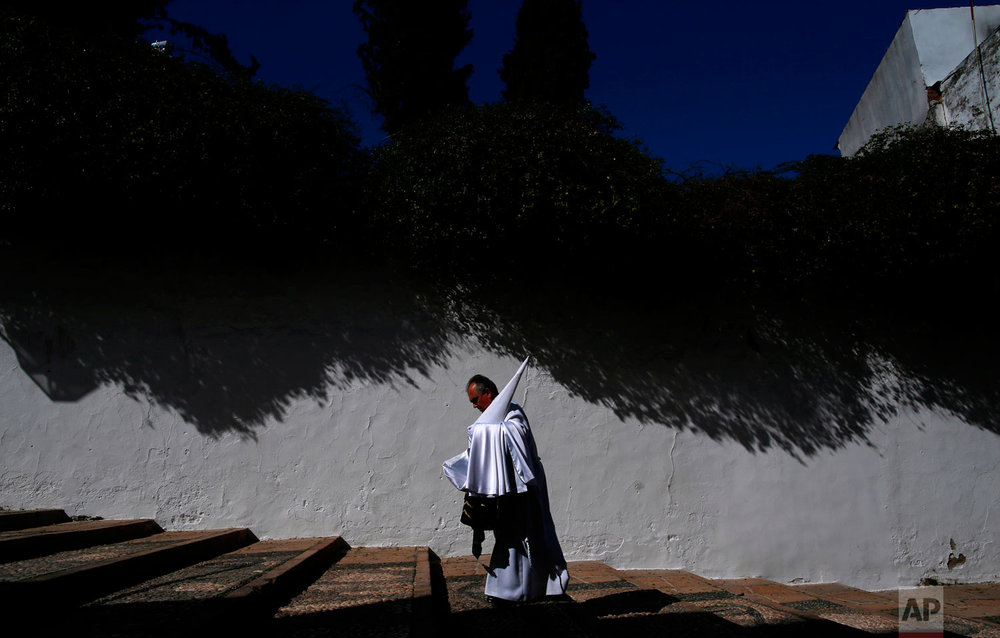 "A penitent from the ""La Paz"" brotherhood walks to the church prior of the Holy Week procession in Cordoba, southern Spain, Wednesday, March 28, 2018. Hundreds of processions take place throughout Spain during the Easter Holy Week. (AP Photo/Manu Fernandez)"