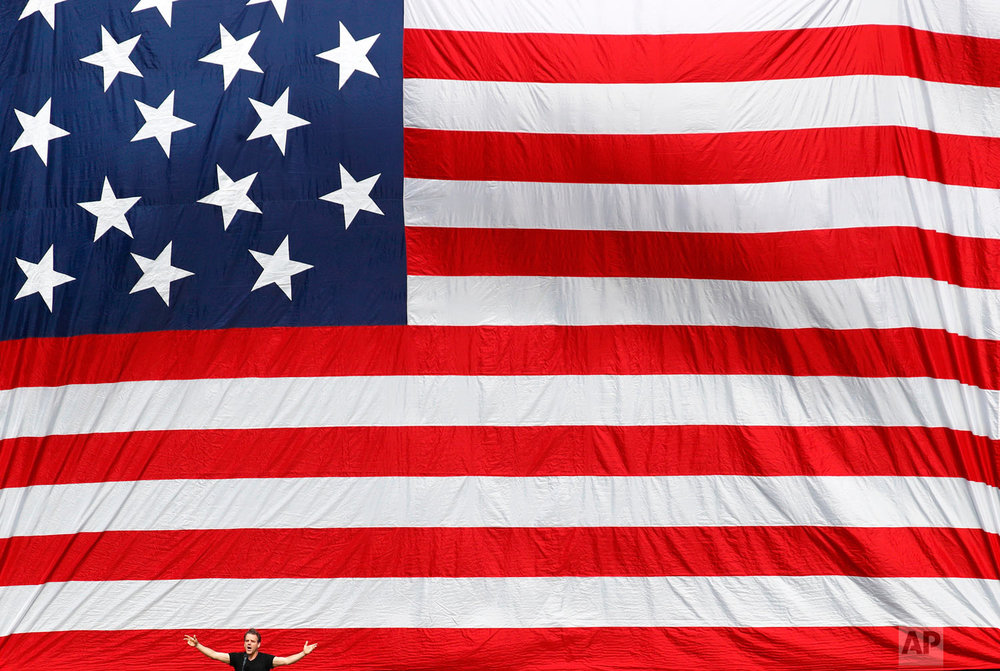 Tenor Richard Troxell sings a rendition of the national anthem in front of a giant U.S. flag before an opening day baseball game between the Minnesota Twins and the Baltimore Orioles in Baltimore on Thursday, March 29, 2018. (AP Photo/Patrick Semansky)