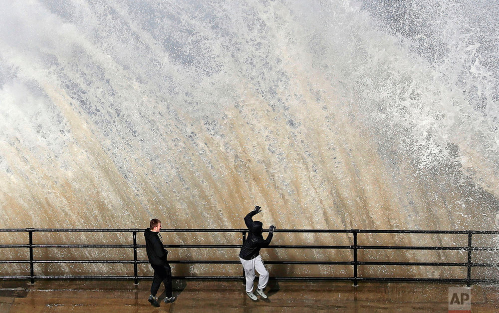 A giant wave crashes next to youths on a sea wall near Cullercoats on the North East Coast of England, Thursday, March 29, 2018, as the weather is set to take a cold turn over the Easter weekend. (Owen Humphreys/PA via AP)