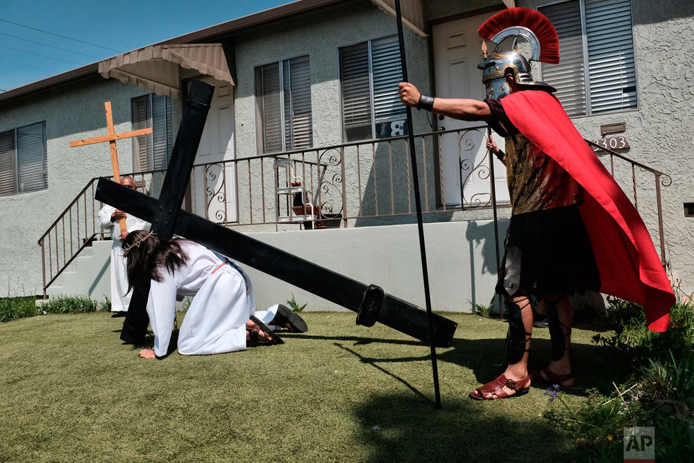 An actor playing the role of Jesus Christ, carries a cross reenacting the crucifixion in the front yard of a home during a Good Friday procession in the Boyle Heights section of Los Angeles on Friday, March 30, 2018. (AP Photo/Richard Vogel)