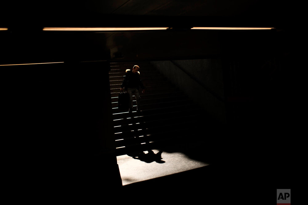 A man walks down a stairway to enter the Colon subway station in Madrid, on Monday, March 26, 2018. (AP Photo/Francisco Seco)