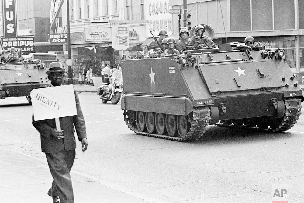 "A striking Memphis sanitation worker walks with a placard that reads ""Dignity"" as National Guard soldiers drive down the street, March 29, 1968 in Memphis, Tenn. (AP Photo/Jack Thornell)"