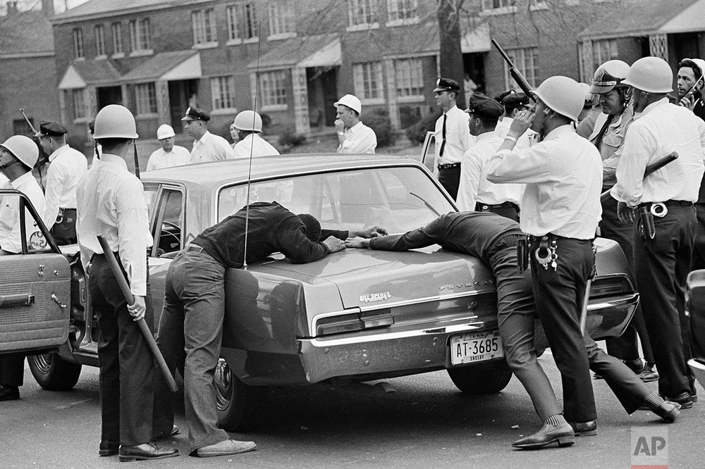 Holding two looting suspects against the trunk of a police car, city and state police officers move out to enforce a curfew in Memphis, Tenn., March 28, 1968. City officials imposed a curfew throughout the city to begin at 7 p.m. (AP Photo/Jack Thornell)