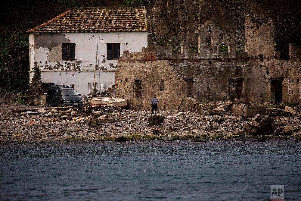 A man stands near the shore next to La Linea de la Conception in Cadiz province. (AP Photo/Emilio Morenatti)