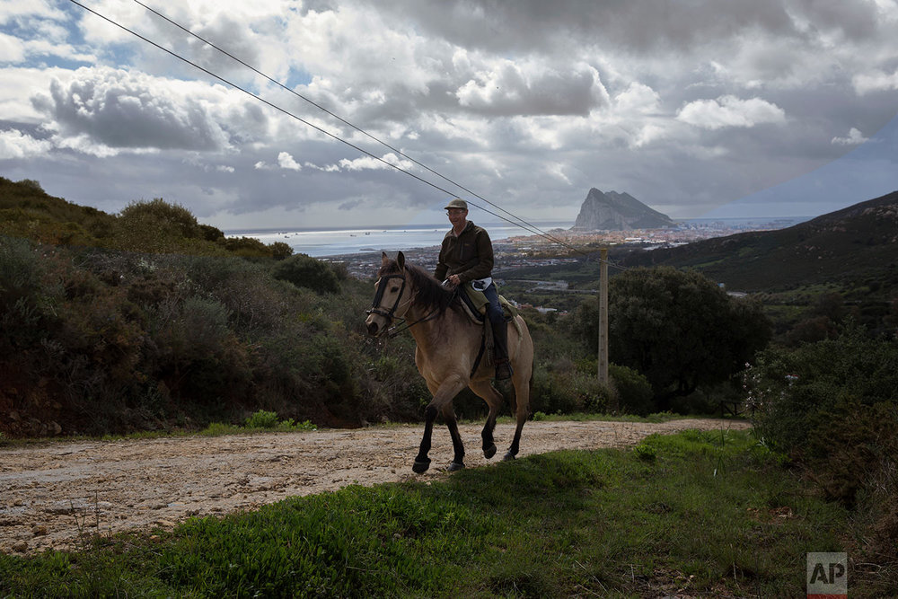 A man rides a horse backdropped by the Gibraltar's Rock and the town of La Linea de la Concepcion, in Cadiz province, south of Spain.  (AP Photo/Emilio Morenatti)